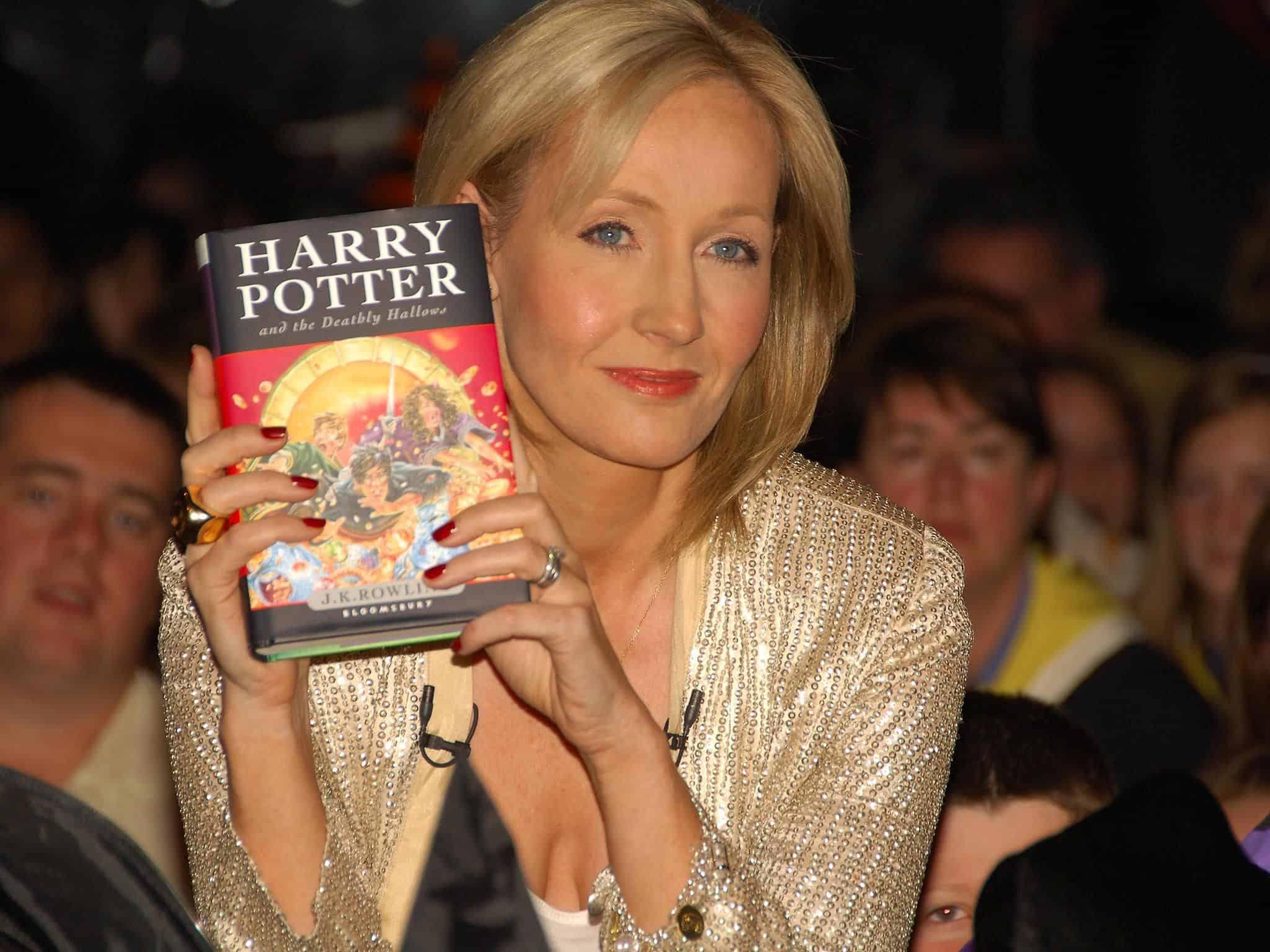 JK Rowling segurando livro de Harry Potter