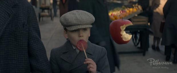 Uma maçã parece estar sendo comida por si mesma enquanto um garoto bastante confuso a encara