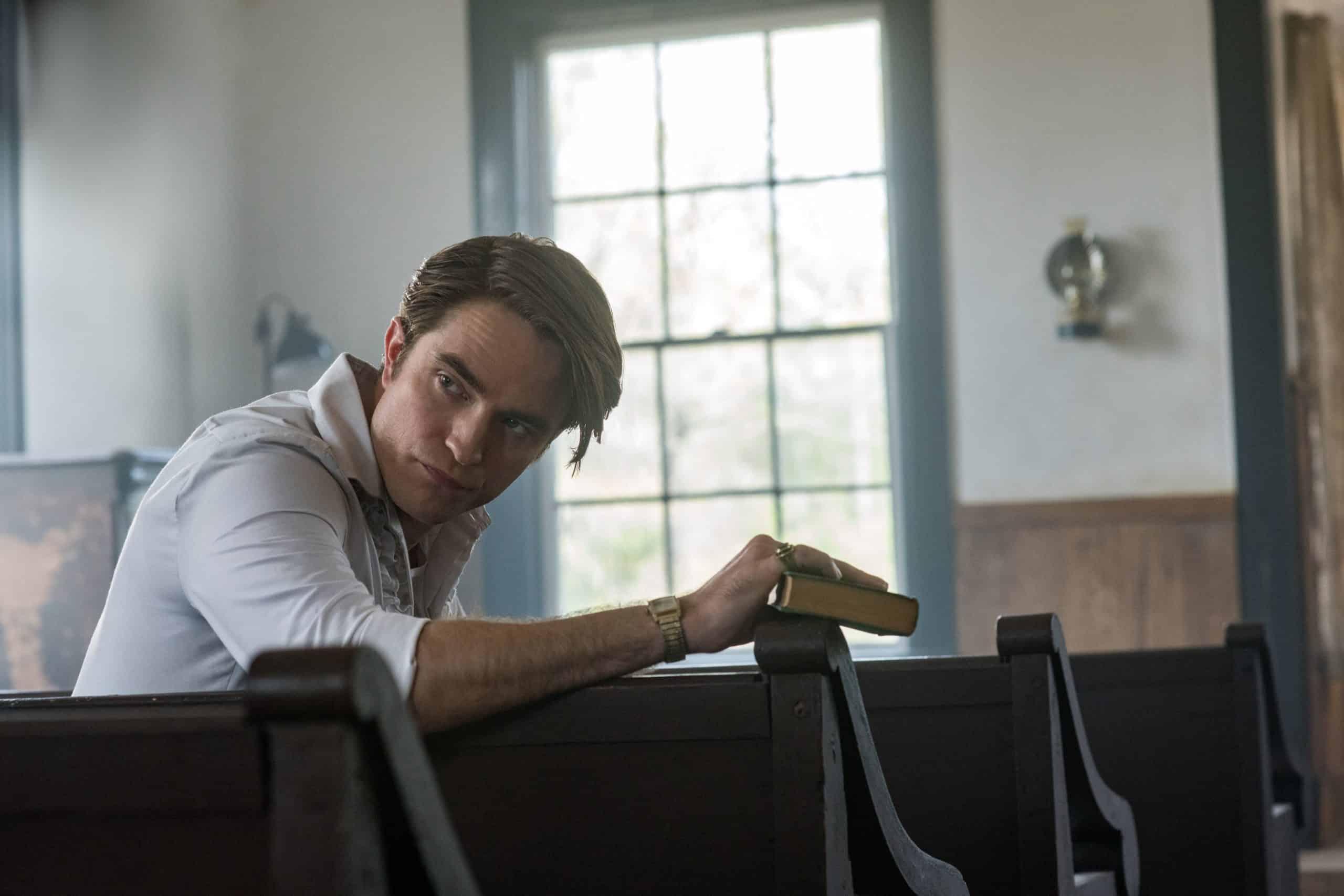 Robert Pattinson segura uma bíblia sentando no banco de uma igreja