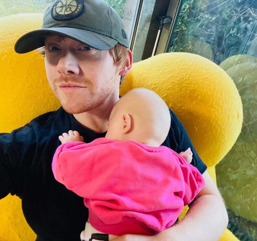 Rupert Grint holds his daughter's lap, Wednesday